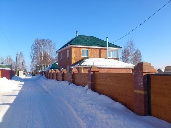 Кирпичный забор зимой как ограждение участка
